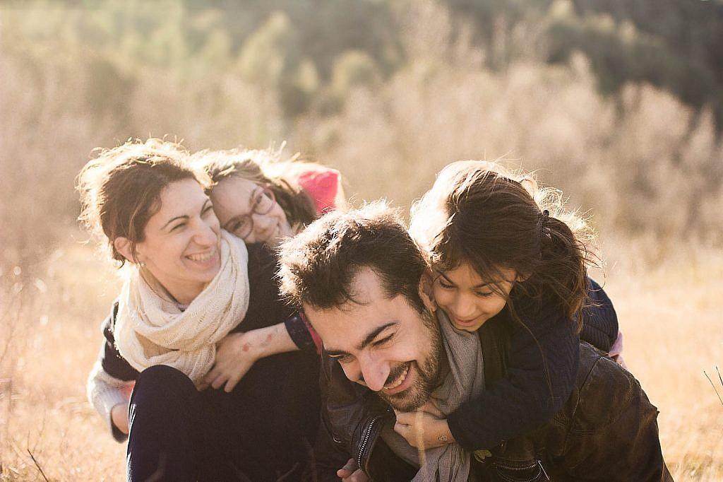Photo d'une famille avec deux petites filles, en pleine nature (couleurs automnales) : des câlins et des rires francs.