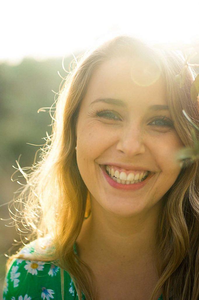 Femme arborant un sourire franc, en contre-jour et illuminée par la lumière du soleil. Teintes jaunes et vertes. Le sourire n'est-il pas la plus belle chose à arborer sur son visage ?